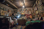 """In April, I sought out Grandma Todorka in the church to give her a copy of her portrait. But the church's priest told me he had to relieve her of her services. She had grown too old and weak to be able to help. So, I visited her at her home. <br /> On this photograph, Grandma Todorka sits on one of the beds in the only room she occupies in her house, where she lives alone. Throughout the years, she had collected many icons. <br /> """"From all the Saints, I love most Jesus Christ,"""" she told me that day, pointing at an icon portraying him. Daily, she enjoyed sitting on her bed and gazing at her icons.<br /> <br /> April 2009"""