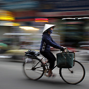 A lady rides a bike in the old quarter of Hanoi, Vietnam. Hanoi is the capital of Vietnam and the country's second largest city. Hanoi, Vietnam. 17th March 2012. Photo Tim Clayton