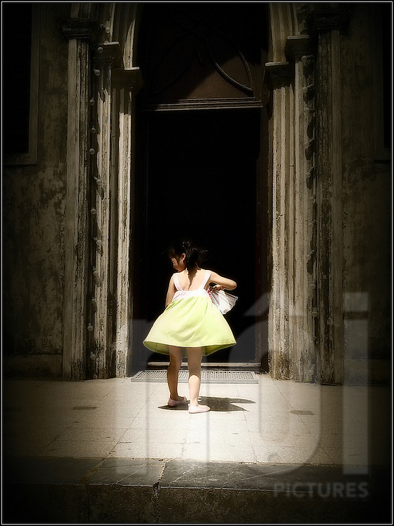 A young vietnamese kid carefree spins outside St Josheph Cathedral, Hanoi, Vietnam, Southeast Asia