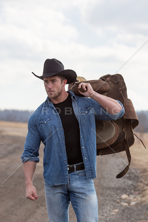 sexy cowboy with a saddle over his shoulder on a ranch