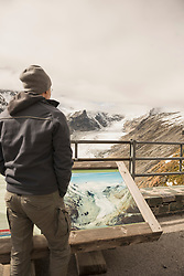 Mature man comparing the melting Grossglockner glacier and stream with a former image in a display cabinet, Glacier Pasterze, Hohe Tauern National Park, Carinthia, Austria
