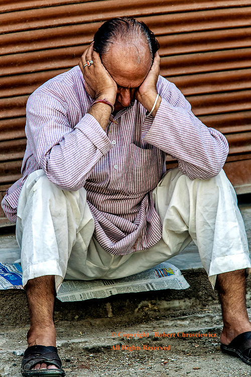 Inconsolable: A man sits inconsolably, on the side of the road, with his head in hand, Jammu India.