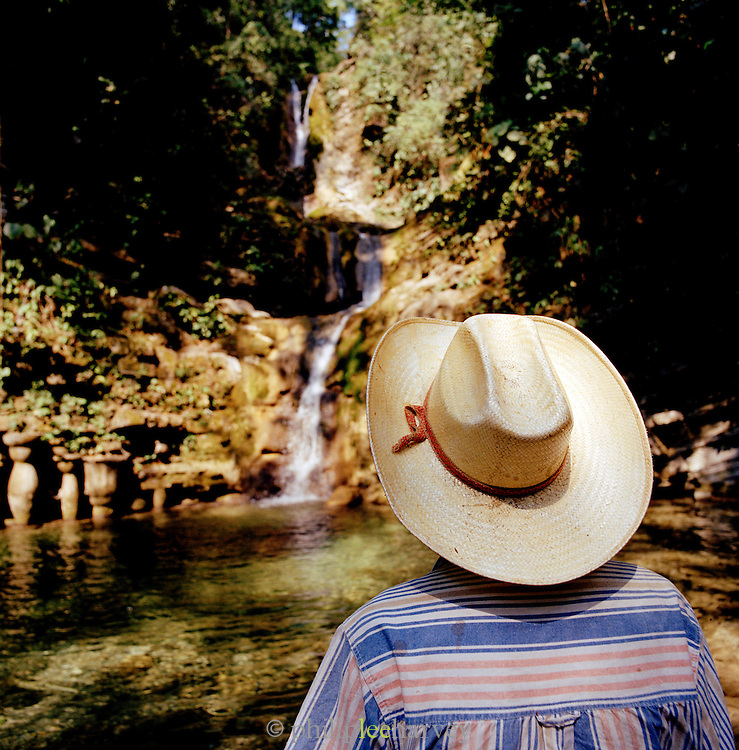 A man in hat standing by a waterfall and pool at the Edward James Surrealist Gardens at Las Pozas, Xilitla, Mexico