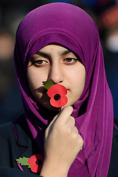 © Licensed to London News Pictures. 11/11/2016. London, UK. Students from Eden Girls School hold poppies during Silence in the Square, a service held in Trafalgar Square, London to mark Remembrance Day. A minutes silence is held on the 11th hour of the 11th day of the 11th month, to recall the end of hostilities of World War I.  Photo credit: Ben Cawthra/LNP