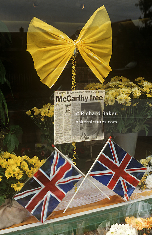 Newspaper cutting, yellow ribbon and Union Jack flags mark the release of Beirut hostage, the TV journalist  John McCarthy. ..John Patrick McCarthy CBE (born 27 November 1956) is a British journalist, writer and broadcaster, and one of the hostages in the Lebanon hostage crisis. He was kidnapped by Islamic Jihad terrorists in Lebanon in April 1986, and held hostage for more than five years. He was appointed a Commander of the Order of the British Empire in 1992. McCarthy was Britain's longest-held hostage in Lebanon, having spent over five years in captivity until his release on August 8, 1991. He shared a cell with the Irish hostage Brian Keenan, for several years.
