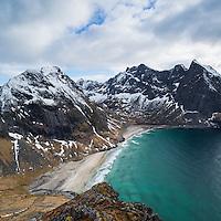 Spring snow and Kvalvika beach seen from Ryten mountain summit, Moskenesoy, Lofoten Islands, Norway