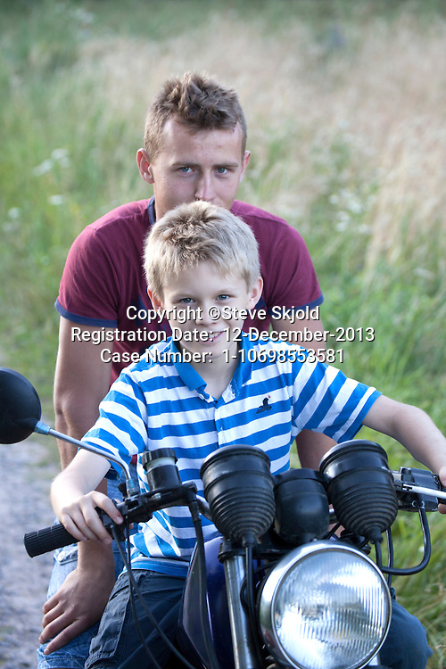 Polish teen giving ride to young happy neighbor boy on his motorcycle age 18 and 10. Zawady Central Poland