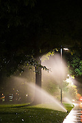 Sprinklers, lit by streetlight, spray water against a tree on the University of Colorado campus in Boulder, Colorado. Watering at night requires less water as less is lost to evaporation.