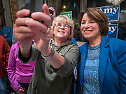 31 OCTOBER 2019 - DES MOINES, IOWA: US Senator AMY KLOBUCHAR (D-MN), right, takes a selfie with a supporter at a restaurant in downtown Des Moines Thursday night during a campaign appearance. Sen. Klobuchar is campaigning to be the Democratic nominee for the US Presidency. Iowa holds the first selection event of the Presidential election cycle. The Iowa caucuses are Feb. 3, 2020.        PHOTO BY JACK KURTZ