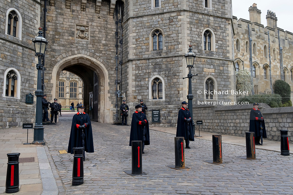 The day after the death at age 99 of Prince Phillip, the Duke of Edinburgh, consort to Queen Elizabeth II, armed police officers and women members of the Royal Household stand outside Windsor Castle where the Queen has been isolating throughout the Coronavirus pandemic, on 10th April 2021, in London, England.