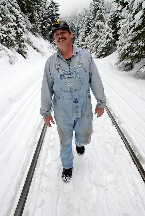 Railroad crew member walking the tracks in winter, Oregon.