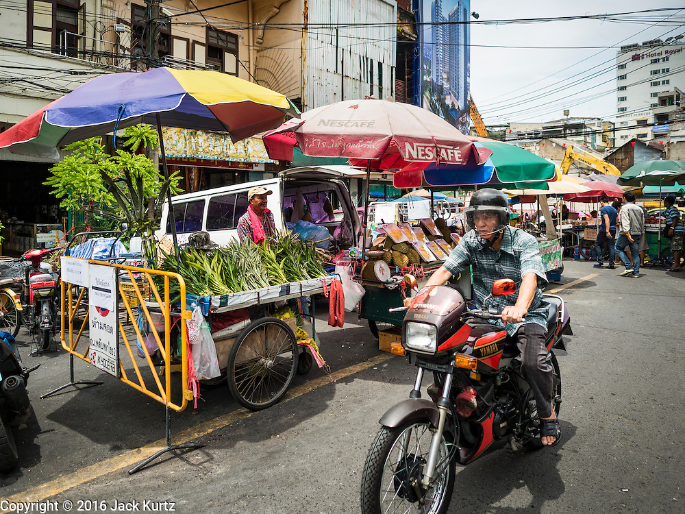 08 JUNE 2016 - BANGKOK, THAILAND:  A man rides his motorcycle through the small produce market at the intersection of Phlap Phla Chai and Chareon Krung Streets in Bangkok's Chinatown neighborhood. The Bangkok Metropolitan Rapid Transit (MRT) system, Bangkok's subway, is being expanded through Chinatown and a station is under construction at the intersection. The small produce market at the intersection will have to move and several of the businesses near the intersection have been evicted to make way for the construction. Bangkok's Chinatown, considered by some to be one of the best preserved Chinatown districts in the world, is changing. Many of the old shophouses are being demolished and replaced by malls and condominium developments.     PHOTO BY JACK KURTZ