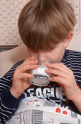 Young boy drinking glass of milk before bed time,