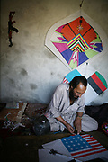 Noor Agha, 52, glues stars with his 'special' glue for a kite ordered by an American client in the house, Kabul, Afghanistan, Monday, July, 9, 2007. Noor Agha is a renowned kite maker who made kites for the movie makers of the best-selling novel, The Kite Runner, which will be distributed by Dreamworks and Paramount Vantage in Nov. this year. Noor Agha's wives, using their special glue, help him produce enough kites to please the clients' needs.