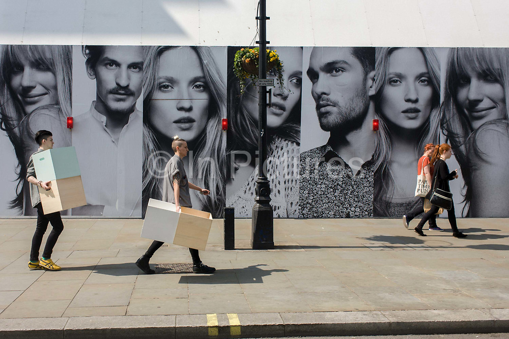 Londoners carry boxes beneath the panels of a large poster for the H&M clothing brand on Regent Street, London. The faces of females and males model look out towards the street in the shopping area north of Oxford Circus where many branded shops line Regent Street. Modelling affordable street fashion we see young, beautiful people represented on the billboard, their clothes all perfect and stylish while the realities of ordinary folk are below.