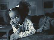 A young african-american girl leans on the back of a couch with a sad look on her face
