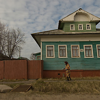 A woman walks by an aging, traditional Russian house that stands by a road leading into the northern port of Arkhangel'sk.