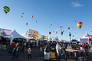 Balloons float overhead at the AARP Block Party at the Albuquerque International Balloon Fiesta in Albuquerque New Mexico USA on Oct. 8th, 2018.