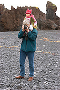 Icelandic man with Chinese baby on his shoulders taking a photo on the rocky beach near Stykkisholmur, Iceland.