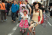 Mother and daughter in cowgirl outfits, riding on their scooters.