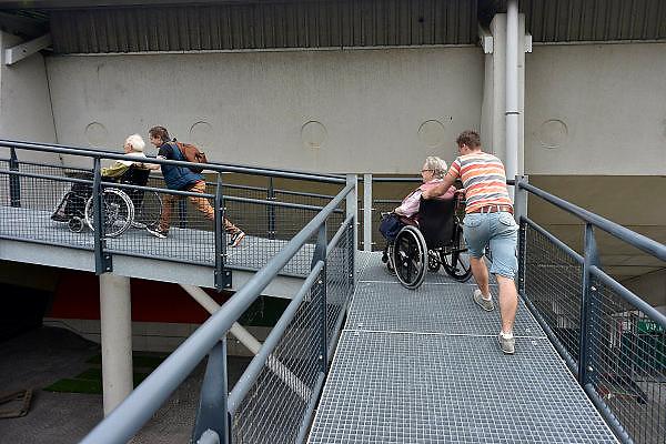 Nederland, Nijmegen, 20-5-2014Jongens van een middelbare school uit Wijchen lopen helpen ouderen in een rolstoel bij een bezoek aan het goffertstadion en voetbalclub NEC.  Hieros wil jongeren kennis laten maken met maatschappelijke organisaties. De scholieren bezoeken in vier dagen onder meer de brandweer, het asielzoekerscentrum en Pluryn.Voor het eerst heeft Hiero s leerlingen zo'n zeventig ouderen laten begeleiden, die de dagbesteding van de StichtingWelzijn Ouderen Nijmegen bezoeken, tijdens het uitstapje gisteren naar voetbalclub NEC. Zij vervullen hiermee hun maatschappelijke stage.Foto: Flip Franssen