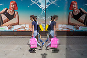 Young women shoppers walk past a female model in an advert outside the London location of the Selfridges Department store on Oxford Street, on 2nd July 2019, in London, England.