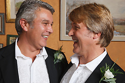Two men at their Civil Ceremony smiling at each other