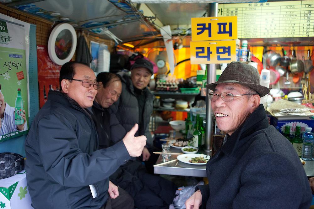 Group of Korean male friends spending free time in Haeundae beach kiosks / Busan, South Korea, Republic of Korea, KOR, 13 February 2010.