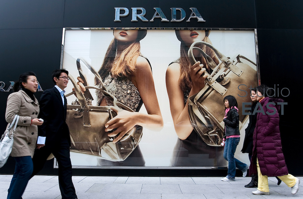 SHANGHAI, CHINA - April 13: Middle-class white-collars walk pass a Prada giant advertisement on April 13, 2010 in Shanghai, China. (Photo by Lucas Schifres/Getty Images)