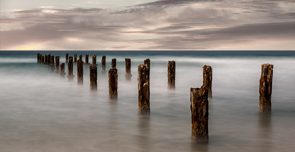 Wood pilings in the sea off the shore in Bet Yannai, Israel.<br /> Long exposure landscape shot.