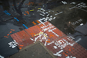 Utilities spray paint markings on the ground, creating a weird patchwork of colour and numbers. London, UK.