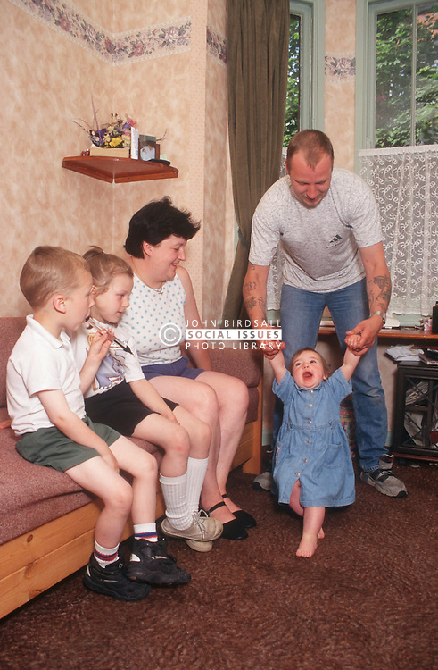 Family group with young child learning to walk,
