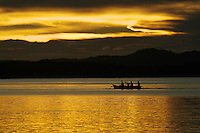 A canoe passes Gam island at sunset.
