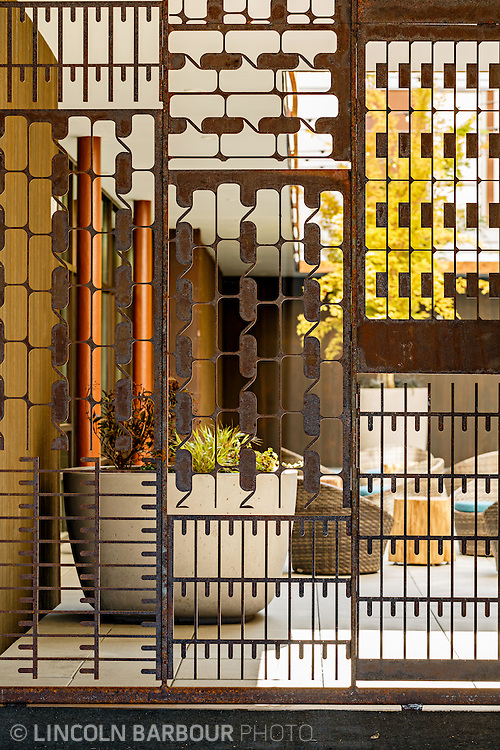 University House student housing apartment in Eugene, OR. Designed by Mahlum Architects. An intentionally rusty iron gate with interesting patterns cut out of it.  A view of a courtyard behind it.