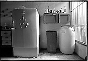 Kitchen with old appliances and water storage barrel.