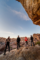 Silhouette of people watching sunset on edge or rock ledge, Hueco Tanks State Park & Historic Site, El Paso, Texas. USA.