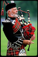 Bearded piper blows on his bagpipe during performance at the Highland Games in Inverness. Scotland