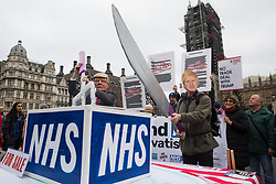 London, UK. 25 November, 2019. Activists wearing Donald Trump and Boris Johnson masks prepare to carve up the NHS during a protest by campaigners from Keep Our NHS Public, Health Campaigns Together, We Own It and Global Justice Now in Parliament Square to call on Prime Minister Boris Johnson to end privatisation of healthcare in the National Health Service (NHS).