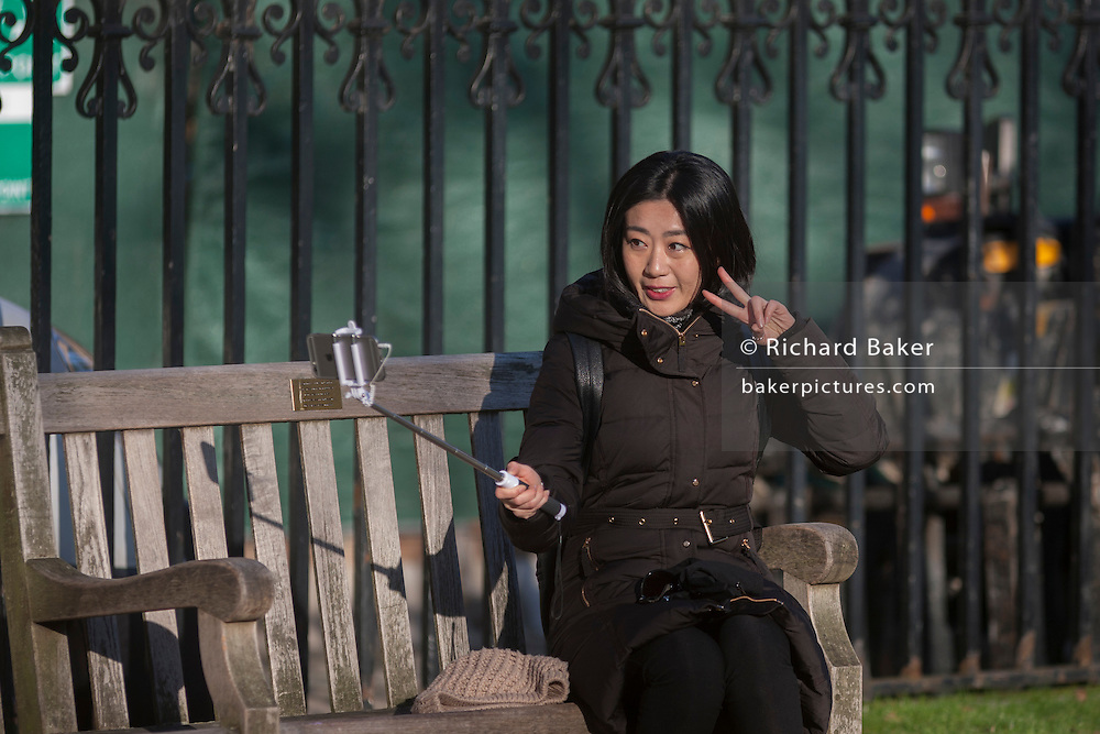 A narcissistic Asian tourist poses for her own camera while seated on a bench, on 18th January 2017, in Parliament Square, London England.