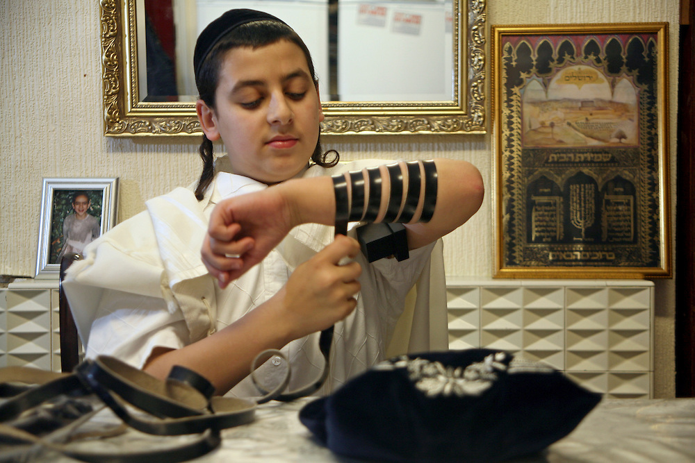 """A young Orthodox Jewish boys preparing to pray by wrapping the leather strap of his Tefillin around his arm and a Tallit (prayer shawl) around his shoulders.  The arm-Tefillin, is worn on the upper arm, while the head-Tefillin, is placed above the forehead. They serve as a """"sign"""" and """"remembrance"""" that God brought the children of Israel out of Egypt. According to Jewish Law, they should be worn during weekday Morning Prayer services."""