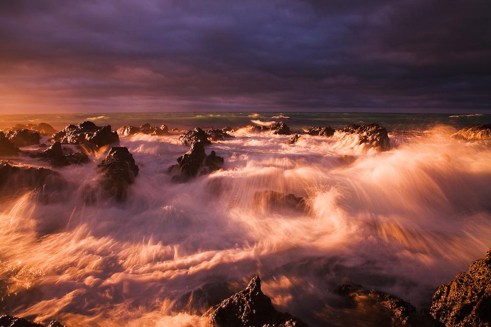 Dramatic sky over rocky coastline at sunrise, South Island, New Zealand