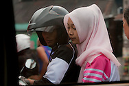 A young Indonesian couple on a motorcycle.<br /> Various scenes of the city of Jakarta in Indonesia.