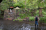 Gentleman enjoying standing in the River Cole at the end of his garden in the inner city area of Sarehole, Birmingham under Coronavirus lockdown on 30th April 2020 in Birmingham, England, United Kingdom. He has been placing sticks nearby for Kingfishers to use, but hasnt seen one for 30 years, and just enjoys being here on his little stretch of river. Coronavirus or Covid-19 is a new respiratory illness that has not previously been seen in humans. While much or Europe has been placed into lockdown, the UK government has put in place more stringent rules as part of their long term strategy, and in particular social distancing.