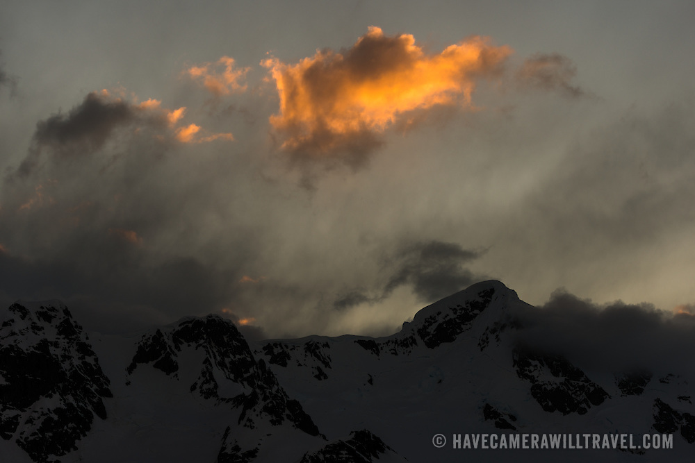 The golden rays of the setting sun catch a cloud above a mountain range in Antarctica.