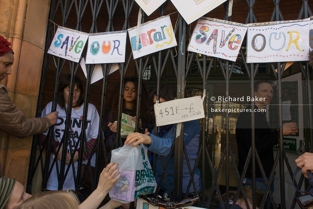 Campaigners protesting the closure by Lambeth council of Carnegie Library pass food supplies through the front gates in Herne Hill, south London on 2nd April 2016. The angry local community in the south London borough have occupied their important resource for learning and social hub for the weekend. After a long campaign by locals, Lambeth have gone ahead and closed the library's doors for the last time because they say, cuts to their budget mean millions must be saved. A gym will replace the working library and while some of the 20,000 books on shelves will remain, no librarians will be present to administer it. London borough's budget cuts mean four of its 10 libraries will either close, move or be run by volunteers. (Photo by Richard Baker / In Pictures via Getty Images).
