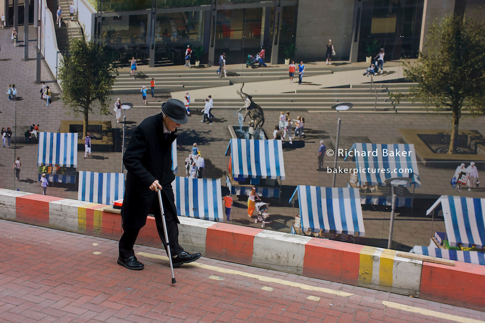Elderly man walks bent past a regeneration project hoarding image at Elephant & Castle, London borough of Southwark.