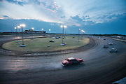 Competitors in the Pure Stock race class run qualifying laps as the sun sets at Salina High Banks Speedway.