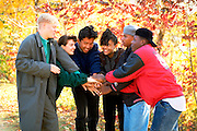 Racially mixed teens with Korean exchange student age 15 in circle with hands joined together.   St Paul Minnesota USA