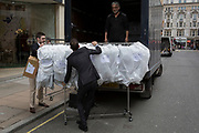 Two men load a rack of covered clothing stock on to a lorry in Bond Street, on 1st May, in London, England.