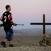 PALM DESERT, CA, OCTOBER 21, 2006: Louisa Prudhomme, mother of Anthony Prudhomme who was the murder victim in a hate crime by Latino gang members in Highland Park, CA, regularly visits the site where she buried her son's ashes. Anthony's brother brought a BB gun with him on a recent visit to the grave site. Located about 150 miles from her home, Anthony's ashes lay buried beneath a cross high atop a hill overlooking the Coachella Nature Preserve. This was a favorite spot for Anthony. (Photograph by Todd Bigelow/Aurora).